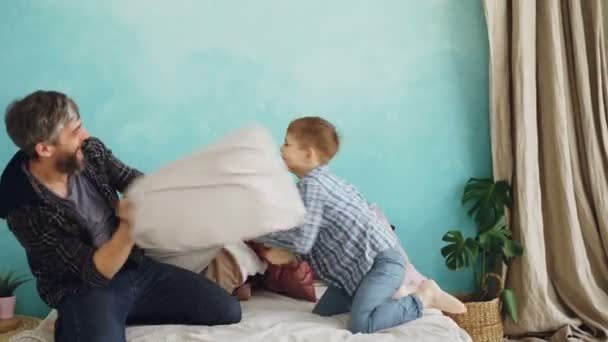 Cheerful father adult bearded man and playful little son are having fun during pillow fight on full-size bed. Happy family, parenthood and free time concept.