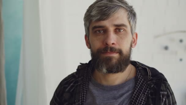 Detailní portrét pohledný vousatý muž s hnědýma očima a šedivý vlasy nosí ležérní oblečení a při pohledu na fotoaparát. Lidé a interiér konceptu.