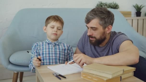 Aranyos gyermek már belefáradt a tanulás és a szórakozás, míg a gondoskodó apa motiválja őt, hogy a házi feladatot, és írni a füzet. Vidám gyermekek és oktatási koncepció.