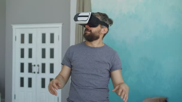 Bearded man in casual clothes is using virtual reality glasses and gesturing while standing in his apartment. Modern technology, entertainment and people concept.