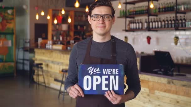Portrait of cheerful handsome young waiter in apron holding we are open sign standing in opening coffee shop. Starting business and successful people concept.