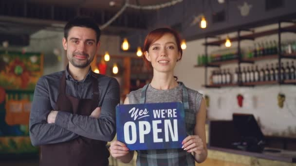 Pretty red-haired businesswoman cafe owner is holding yes we are open sign with her employee in apron standing near her. Successful start-up and people concept.