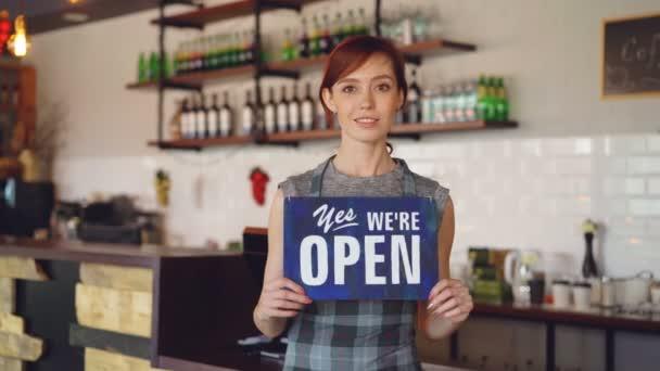 Portrét majitel malé firmy sebevědomá žena držící jsme otevřeni znamení, stojící v její kavárně a usmíval se při pohledu na fotoaparát. Interiér domu kávy v pozadí.