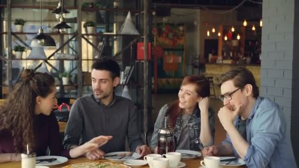 Cheerful young friends are talking and gesturing sharing news while sitting at table in modern cafe. Big pizza, cups and plates, tables and chairs are visible.