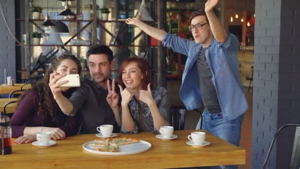 Emotional young people are taking selfie with smartphone posing and laughing inside modern cafe. Modern technology, fun, millennials and friendship concept.