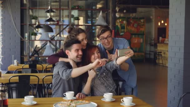 Best friends are taking selfie laughing posing making funny faces and gestures hugging at lunch in cafe. Social media, friendship, millennials and free time concept.