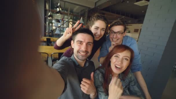 Point of view shot of cheerful group of friends recording funny video in cafe posing and smiling hugging and gesturing. Friendship and happy people concept.