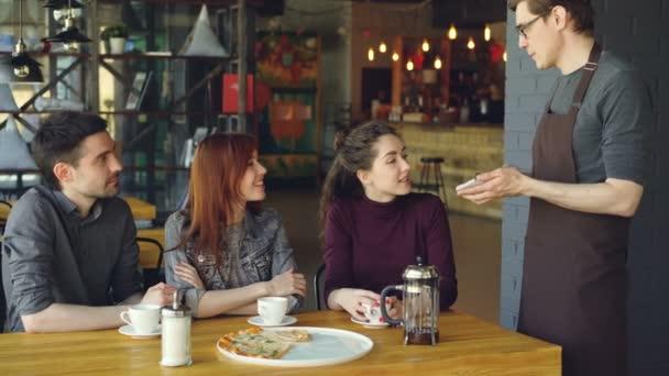 c4a21f2497df86 Freundlicher männliche Kellner nimmt Bestellung von fröhlichen Gruppe von  Freunden am Tisch im Café und im Gespräch. Essen und trinken