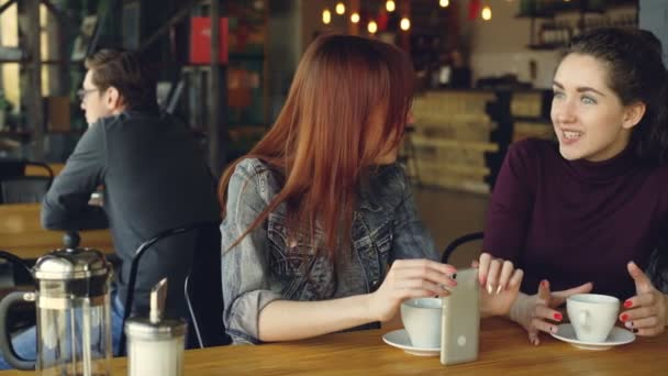 Two attractive women in casual clothes are having girl time in cafe talking and holding coffee cup and smartphone. Nice cafe interior, customers and furniture are visible.
