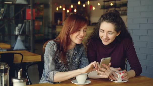 Two young pretty girlfriends are using smartphone in cafe, laughing and talking emotionally. Social media, meeting friends and modern technology concept.