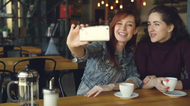 Pretty girls best friends are taking selfie with smartphone then watching photos while drinking coffee in coffeehouse. Friendship, social media and having fun concept.