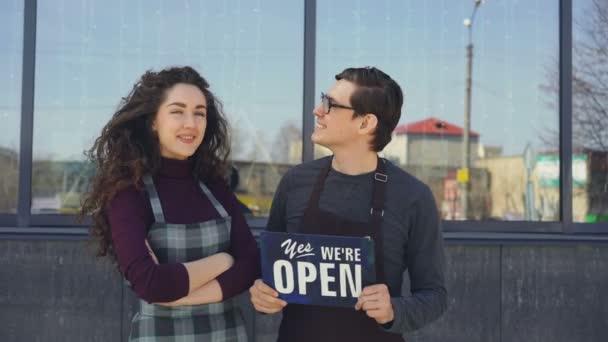 Happy atraktivní číšníci drží otevřené břidlice a při pohledu na okna nově otevřené kavárně pak obrací na kameru a usmívá se. Úspěšné spuštění koncept