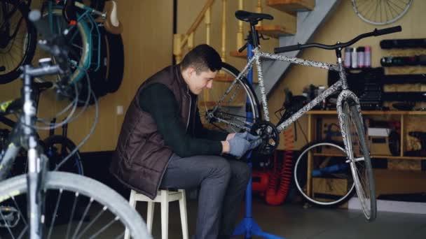 Dollly Shot von fokussierten jungen Mechaniker Reparatur kaputten Fahrrad Lauffläche sitzt auf einem Hocker in der Nähe von modernen Fahrrad am Arbeitsplatz. Wartung, Beruf und Personalkonzept.