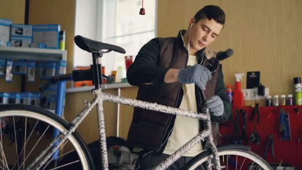 Focused mechanic is assembling bicycle placing handle-bar then tightening joints with key and listening to music through earphones. People and maintenance concept.