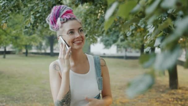 Radostná dívka se zuby rovnátka chatování na mobilním telefonu smích v městském parku