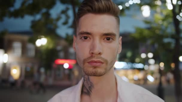 Portrait of stylish guy with tattoo and trendy hairstyle in city street at night