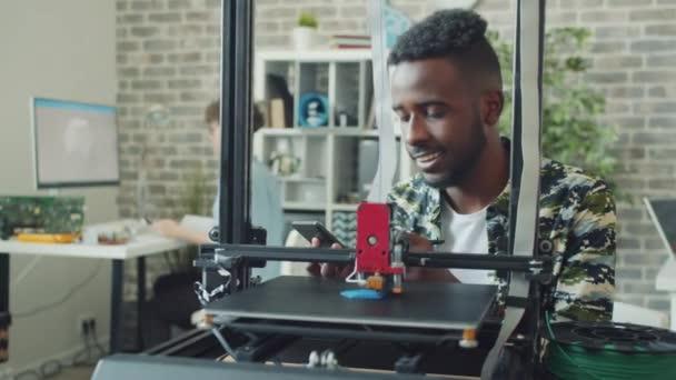 Afroamerikaner nutzt 3D-Drucker im Büro und genießt moderne Technik