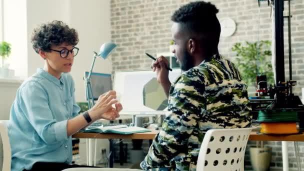 Junge Frau diskutiert mit Afroamerikaner im Amt über 3D-Druck
