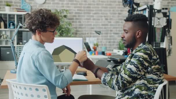 Zeitlupe: Mann und Frau konstruieren Roboterdetails mit 3D-Drucker