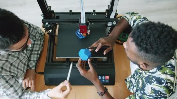 Hochwinkelansicht von Ingenieuren, die 3D-gedruckte Form in der Nähe eines arbeitenden Druckers diskutieren