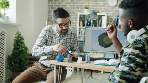Zeitlupe: Männer diskutieren 3D-Druckelemente für Roboter im modernen Büro