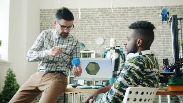 Junge Männer diskutieren 3D-bedrucktes Kunststoffelement im Büro am Arbeitsplatz