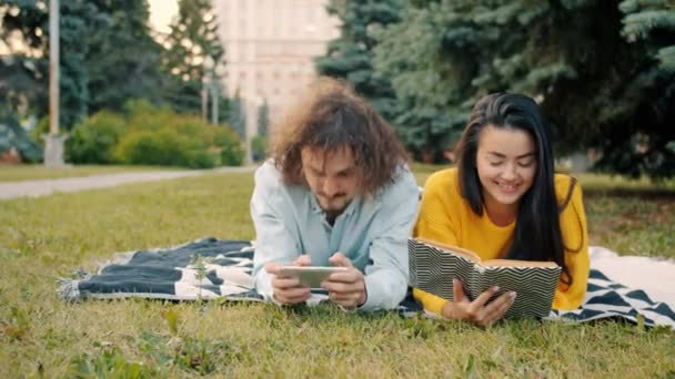Man playing smartphone game while woman reading book outside in urban park
