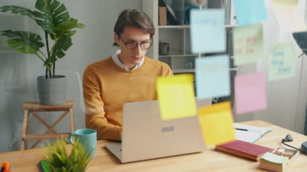 Serious businessman working with laptop behind glass wall with colorful stickers