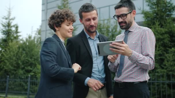 Slow motion of happy young colleagues outdoors discussing work holding tablet