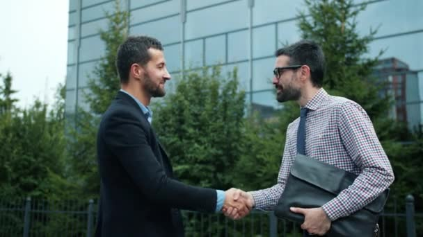 Business partners meeting outdoors in city shaking hands greeting saying hello