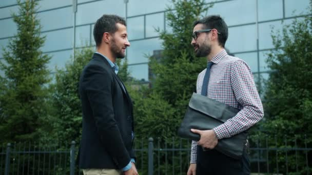 Coworkers successful men shaking hands outdoors saying good-bye then leaving