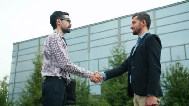 Obchodní partneři muži potřást rukou dělat dohodu stojící venku ve městě