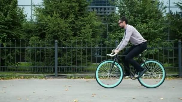 Zpomalení pohybu mladých kancelářských pracovníků jízda na kole do práce v blízkosti obchodního centra