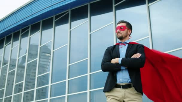 Egy öltönyös, jóképű üzletember portréja Superman jelmezben a szabadban.