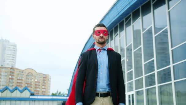 Közepes lövés jóképű Ceo visel Superman köpeny és maszk kívül iroda