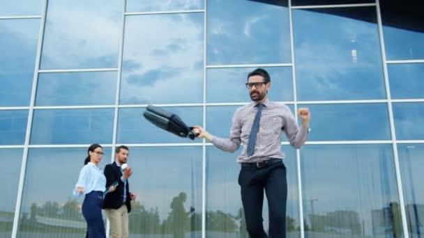 Joyful entrepreneur with briefcase dancing outdoors having fun enjoying success