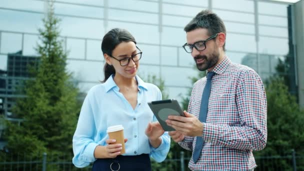 Male and female coworkers talking outside near workplace using tablet computer