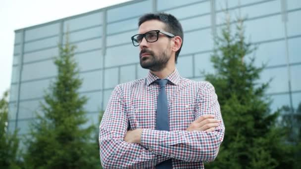 Portré egy jóképű szakállas üzletemberről, aki kint áll az utcán.