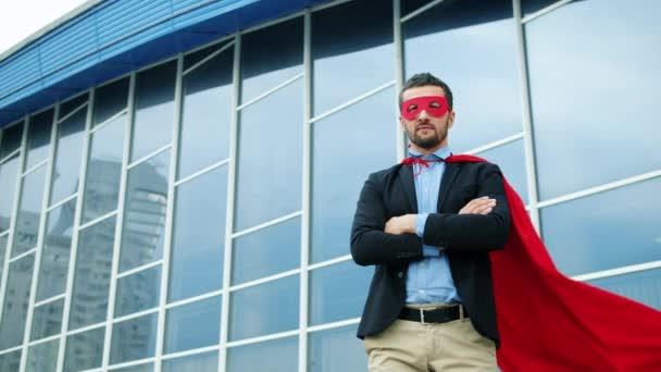 Komoly irodai munkás portréja vörös szuperhős köpenyben és maszkban odakint