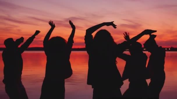 Boldog emberek táncolnak a folyóparton, karokat mozgatnak napnyugtakor.