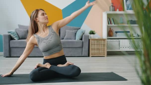 Bezstarostná žena relaxující během cvičení jógy v lotosové poloze se zavřenýma očima