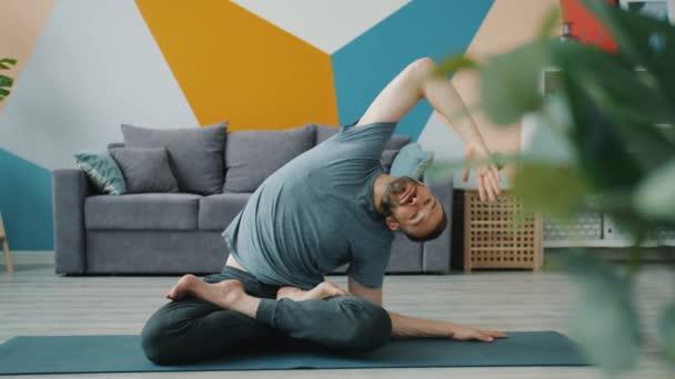 Zpomalení pohybu seriózního muže ohýbajícího se bokem v pozici sedícího lotosu doma