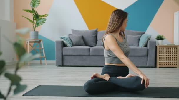 Attractive female adult working out in lotus position at home sitting on yoga mat