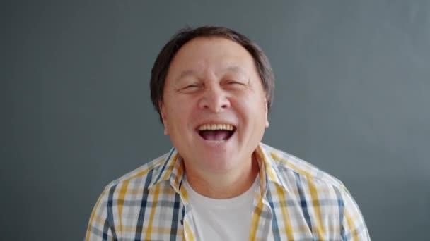 Radostný asijský muž smějící se baví při pohledu na kameru proti šedému pozadí