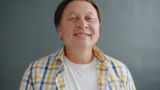 Šťastný asijský muž usměvavý pocit veselý a bezstarostný om šedé pozadí