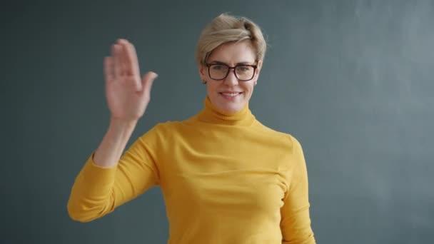 freundliche erwachsene Dame mit Brille winkt lächelnd mit der Hand auf schwarzem Hintergrund