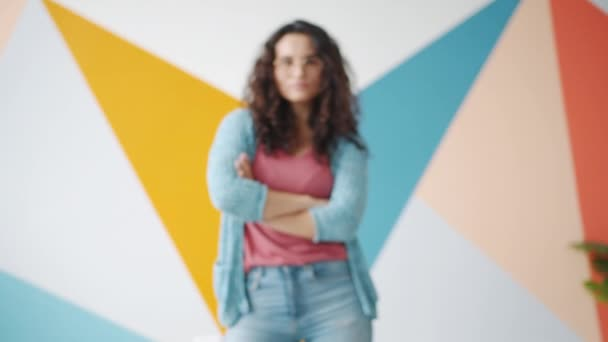 Zoom-in portrait of good-looking mixed race woman standing indoors with arms crossed