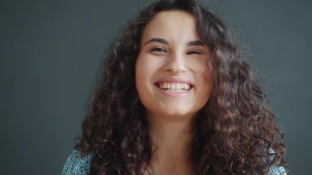 Portrét atraktivní smějící se ženy baví na tmavém pozadí