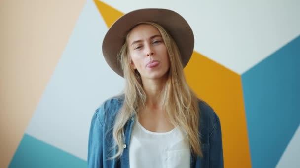 Porträt einer lustigen jungen Frau, die alberne Fratzen auf buntem Hintergrund macht