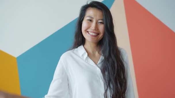 Porträt einer entzückenden jungen asiatischen Dame, die vor buntem Hintergrund mit der Hand wedelt